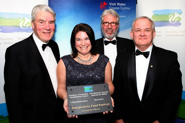 Heather Myers, Chief Executive - Abergavenny Food Festival holds the award. L to r - Sir Trefor Morris, AFF Board Member, Nigel Burton, Chairman of the Board